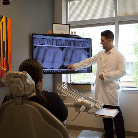 Our dental hygienist showing a patient dental x-rays - one of the many benefits from our dental team