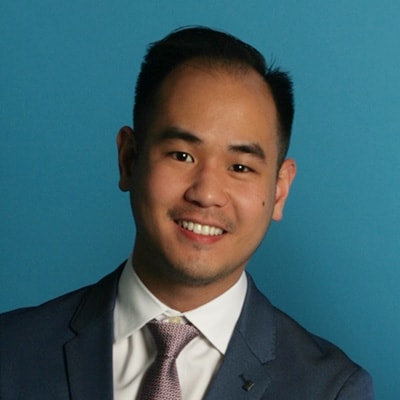 Dr. Jon Vo, a top dentist in Redmond, WA smiling in a dark blue suit coat and tie