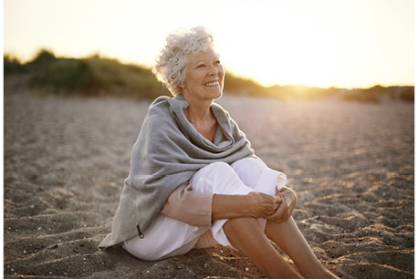Elderly woman sitting on the beach, smiling about Same Day New Smile™ in Kirkland, WA