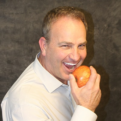 Actual patient of Dr. Shawn Keller's biting into an apple after All-on-4 implants
